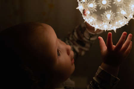 Babies first Christmas. Baby is touching luminous ball very impressed and excited. Dark key, copy space Banco de Imagens