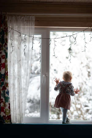 Toddler girl standing on the window decorated for Christmas and watching first snow. New year holidays. Vertical format
