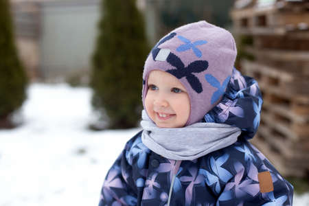 Cheerful smiling girl wearing winter clothes having fun outside in the backyard of the country house. Weather is snowy
