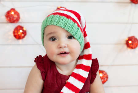Cute baby wearing Christmas hat on decorated for new year white wooden background. First Christmas Red, green and white colors Banco de Imagens
