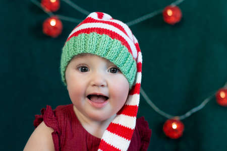 Cute excited baby wearing Christmas hat on decorated for new year dark green background. First Christmas and Christmas sales concept.