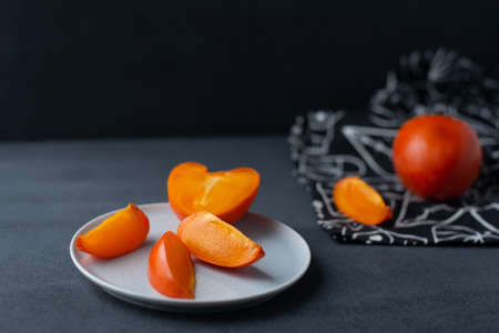 Flat lay with bright orange persimmon on black and white background. Autumn fruits.