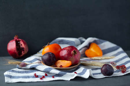 Autumn fruits still-life. Pomegranate, persimmon and plum on dark gray background. Copy space