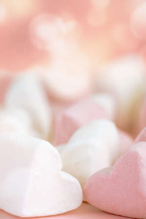 Pink and white marshmallows in the shape of hearts on a pink abstract background with bokeh.