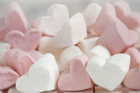 Pink and white marshmallows in the shape of hearts on a white wooden background.