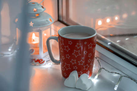 Cozy winter still life with red mug with hot drink, two white heart-shaped marshmallow, candle and garland on window.