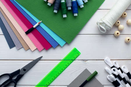 How to make felt flag garland with embroidered letters at home. Step by step instructions. Hands making DIY project. Step 1: prepare felt, moulinet, cardboard, scissors, ruler and rope