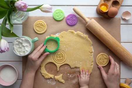 Flat lay with mother and baby hands preparing Easter theme cookies. Spring holidays and family time concept. Rolled dough with ingredients, easter theme stamps, tulips and hands of adult and baby