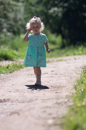 Small cute girl with blond hair wearing dress and rubber rainboots. Girl is walking in the country side. Foot path. Vertical format
