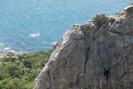 High cliff and small figure of rock climber. Sea is behind. Extreme sport. Spring, Cremea, breathtaking view