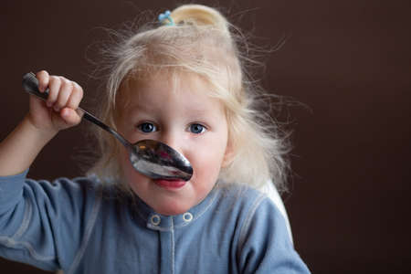 Cute blond toddler girl with blue eyes eating soup using big spoon. Dark background. Girl is wearing blue overall