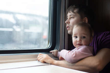 Young man and his mall daughter in the train. Family is staring out of the window. Snowy winter outside. Railway trip