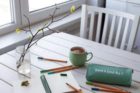 Preparation for drawing in spring morning with fresh leaves and blanc notepad. White and green color. Mental health and self-time concept. Words have a good day on a pencil case
