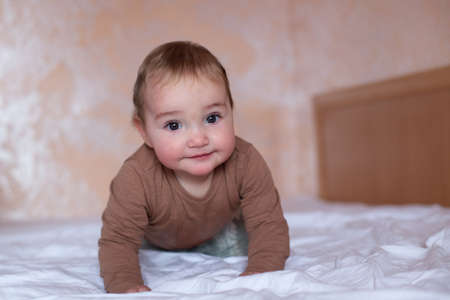 Cute baby crawling on the bed. Calm and natural brown color. Baby in the bedroom Banco de Imagens