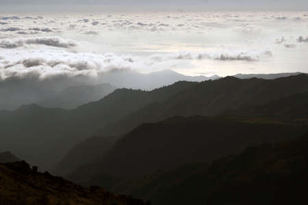 Morning mountain scenery with gradient gray color peaks and low clouds. Sunrise. Portugal, Madeira Banco de Imagens