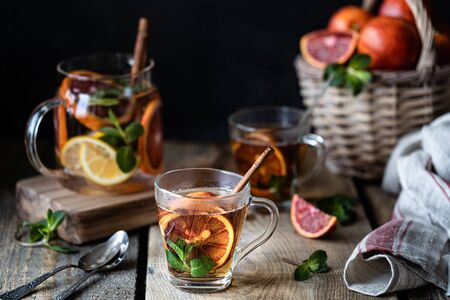 Homemade tea in a transparent glass with red orange and lemon, cinnamon and mint on a wooden background. Oranges Wicker Basket.