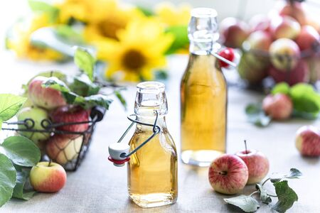 Apple vinegar. Bottle of apple organic vinegar or cider on wooden background. Healthy organic food Imagens