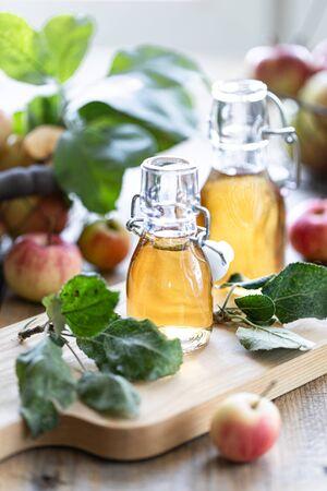 Apple vinegar. Bottle of apple organic vinegar or cider on wooden background. Healthy organic food Stock Photo