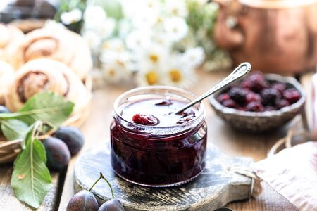 Sweet homemade plum jam and fruits on a wooden table. 写真素材 - 129477692
