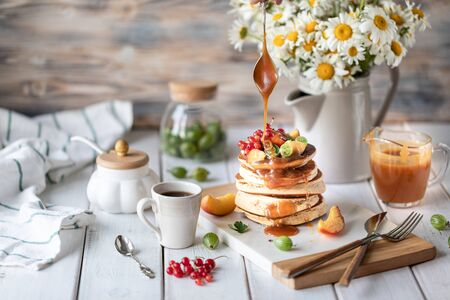 Cornmeal pancakes with salted caramel served with berries and fruits on a white wooden background. 写真素材 - 129477996