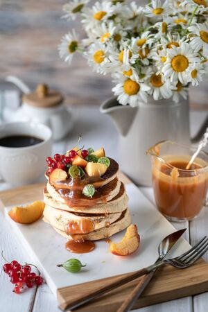 Cornmeal pancakes with salted caramel served with berries and fruits on a white wooden background. 写真素材