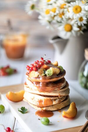 Cornmeal pancakes with salted caramel served with berries and fruits on a white wooden background. Rustic 写真素材 - 129478004