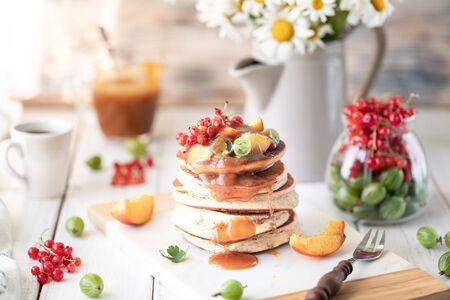 Maïsmeel pannenkoeken met gezouten karamel geserveerd met bessen en fruit op een witte houten achtergrond. Rustiek Stockfoto