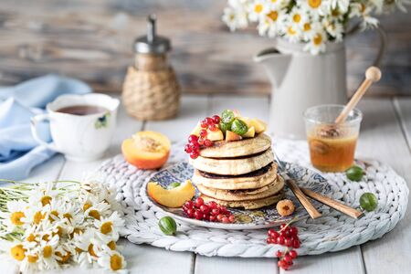 Cornmeal pancakes with honey, served with berries and fruits on a white wooden background. Rustic