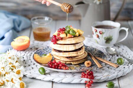 흰색 나무 배경에 베리와 과일을 곁들인 꿀을 곁들인 옥수수 가루 팬케이크. 촌사람 같은
