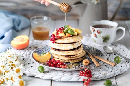 Cornmeal pancakes with honey, served with berries and fruits on a white wooden background. Rustic 写真素材 - 129478348