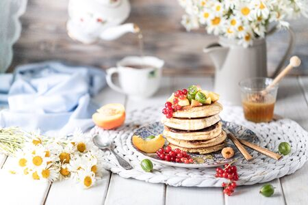 Cornmeal pancakes with honey, served with berries and fruits on a white wooden background. Rustic 写真素材 - 129478353