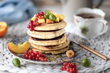 Cornmeal pancakes with honey, served with berries and fruits on a white wooden background. Rustic 写真素材 - 129478365
