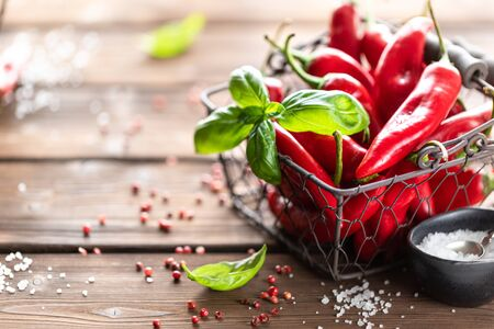 Red chili peppers with a sprig of basil in a wicker metal basket on a wooden background