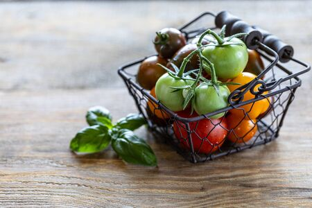 Metal basket with ripe different red, yellow and green tomatoes on a wooden table