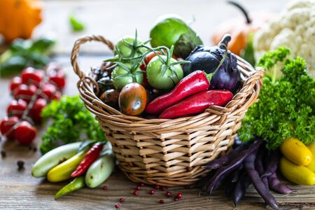 Autumn harvest of vegetables in a wicker basket: tomatoes, beans, squash, pumpkin, cabbage, greens, parsley