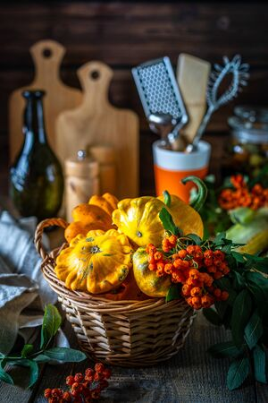 Autumn vegetables on a wooden table: pumpkin, orange pepper, paprika, mushrooms, corn, sweet potato yam, squash, cauliflower, broccoli tomatoes herbs basil
