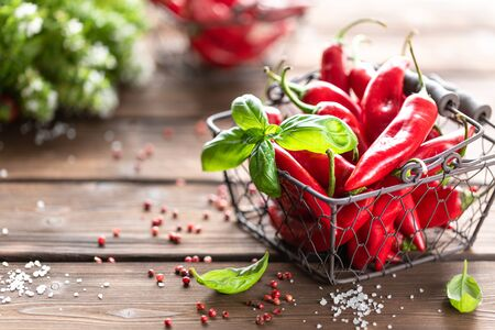 Red chili peppers with a sprig of basil in a wicker metal basket on a wooden background 写真素材