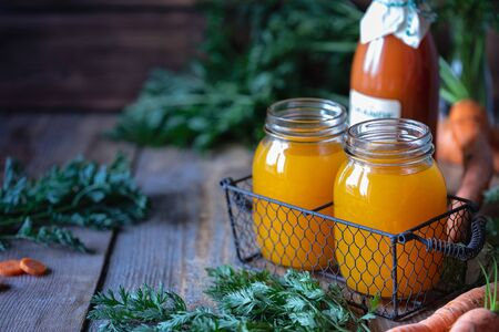 Healthy food. Carrots and carrot juice in a glass jar in a metal basket on a dark wooden background. Copy space