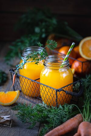 Healthy food. Carrots and carrot juice with orange in a glass jar in a metal basket on a dark wooden background. Copy space