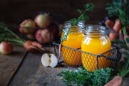 Healthy food. Carrots and carrot juice with apple in a glass jar in a metal basket on a dark wooden background. Copy space