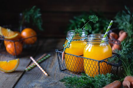 Healthy food. Carrots and carrot juice with orange ginger in a glass jar in a metal basket on a dark wooden background.
