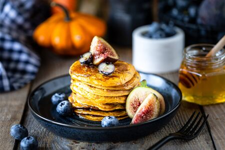 Pumpkin pancakes with syrup or honey, flax seeds, figs, blueberries in a dark plate on the table 写真素材