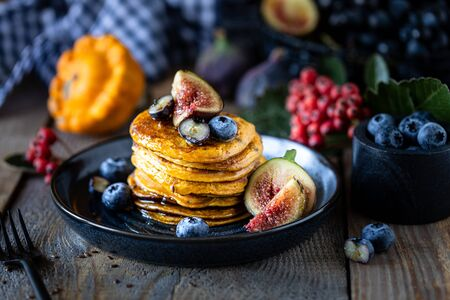 Pumpkin pancakes with syrup or honey, flax seeds, figs, blueberries in a dark plate on the table, selective focus 写真素材