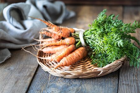 Organic carrots on a wicker tray, on a wooden dark background. Rustic natural style.