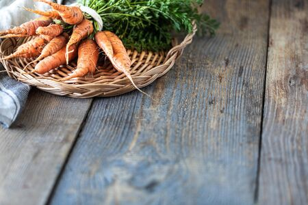 Organic carrots on a wicker tray, on a wooden dark background. Rustic natural style. copy space.