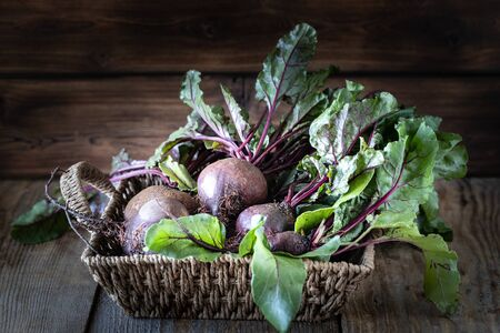 Fresh organic red beets with leaves in a wicker basket on a wooden table. Natural organic vegetables. Autumn harvest. Rustic country style. 写真素材
