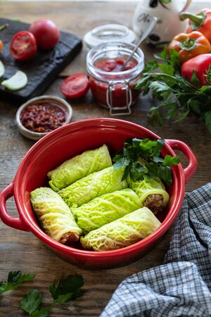 savoy cabbage rolls stuffed with meat, rice and vegetables on a rustic table. 写真素材