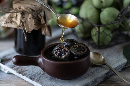 Jar of walnut jam on a wooden table and a group of green walnuts