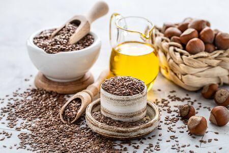 Aceite de nuez y linaza en una botella y cuenco de cerámica con semillas de lino marrón y una cuchara de madera sobre un fondo blanco. Foto de archivo