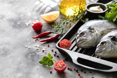 Due pesci dorado crudi con spezie, limone e prezzemolo in una padella per grigliare nera su uno sfondo di cemento bianco. Copia spazio